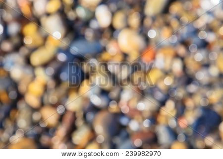 Blurred background of a sea stone beach. Blurred drops of water on the sea pebbles. Summer coast background. Warm pebbles and the beautiful sea. stock photo