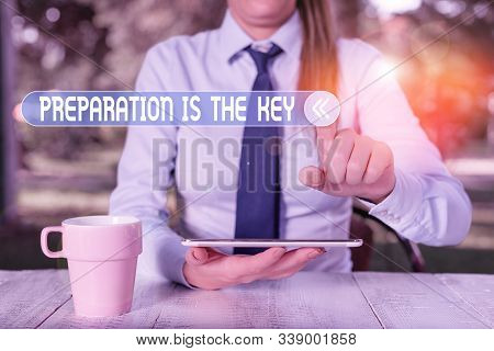 Handwriting text writing Preparation Is The Key. Concept meaning it reduces errors and shortens the activities Female business person sitting by table and holding mobile phone. stock photo