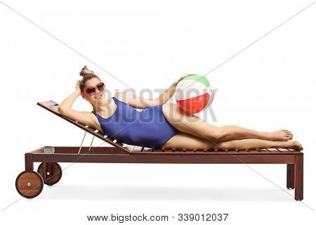 Full length shot of a woman with sunglasses on a sunbed holding a beach ball isolated on white background stock photo