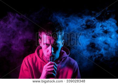 Close up portrait of the face of an adult serious man exhales blue toxic smoke while smoking e-cigarette and vape illuminated with pink colored light on a black background. Harm to health. stock photo