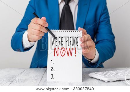 Text sign showing We Re Hiring Now. Conceptual photo recently employ someone or pay someone to do particular job Man holds empty paper with copy space in front of him Copy Space. stock photo