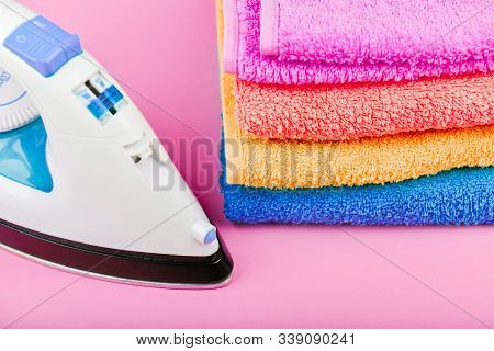 The concept of ironing clothes. House order. Iron and ironed fabric. Electric iron on a pink background with towels. multi-colored towels. stock photo