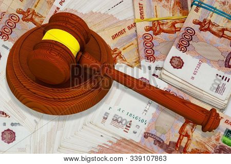 Litigation on finance. Judge or auction hammer lies on Russian banknotes. 3D Illustration stock photo