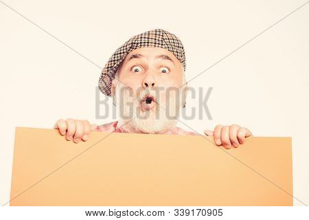Senior bearded man place announcement on banner. Advertisement shop. surprised mature man in retro hat. Advertisement. job search. Need help. wanted. Copy space placate information. what a surprise stock photo