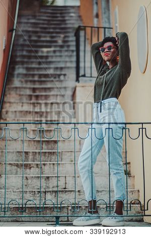 Vertical shot of a charming elegant African young woman at the bottom of the stairs; a dazzling fancy black hipster girl in sunglasses, pullover, and jeans next to the stone narrow outdoor stairway stock photo