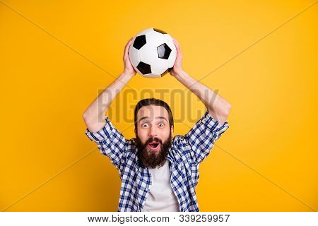 Portrait of nice attractive cheerful cheery funky addicted bearded guy fan in checked shirt holding in hands over head ball having fun isolated over bright vivid shine vibrant yellow color background stock photo