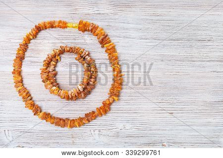 top view of rough amber necklace and bracelet on gray wooden board with copyspace stock photo