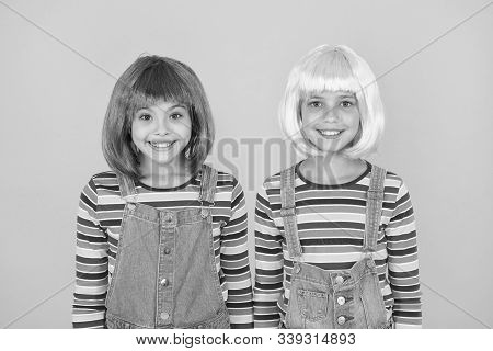 Modern fashion is created to enjoy. Happy girls wear fashion hair wigs yellow background. Little children smile in casual fashion style. Fancy fashion. Beauty and hair salon. stock photo