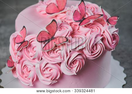 Overhead view of a freshly baked cake decorated with pink icing sugar roses displayed on a cake stand over a black background with copyspace. stock photo