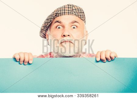 Senior bearded man place announcement on banner. scared mature man in retro hat. Advertisement. Advertisement shop. wanted. Copy space placate information. job search. Need help.ad od feeling stock photo