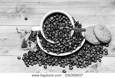 Cup full coffee brown roasted bean blue wooden background. Caffeine concept. Cafe drinks menu. Coffee break with oat cookie. Fresh roasted coffee beans. Beverage for inspiration and energy charge stock photo