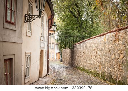 Novy Svet Street, an empty picturesque cobblestone medieval and narrow street of Hradcany hill in Prague, Czech Republic, with medieval houses and trees. It is a major touristic attraction. stock photo