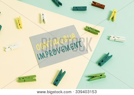 Conceptual hand writing showing Continuous Improvement. Business photo showcasing ongoing effort to improve products or processes Colored clothespin paper reminder with yellowblue background. stock photo