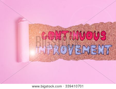 Handwriting text Continuous Improvement. Concept meaning ongoing effort to improve products or processes Cardboard which is torn in the middle placed above a wooden classic table. stock photo