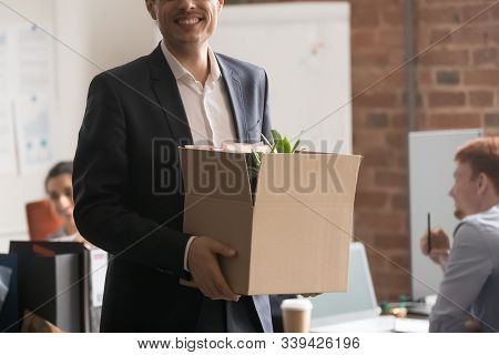 Cropped image happy newcomer standing holding box with belongings stock photo