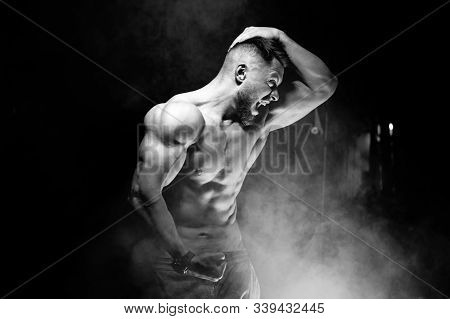 Strong brutal bodybuilder man with perfect abs, shoulders, biceps, triceps and chest showing his biceps. Scream motivation. Black and white. stock photo