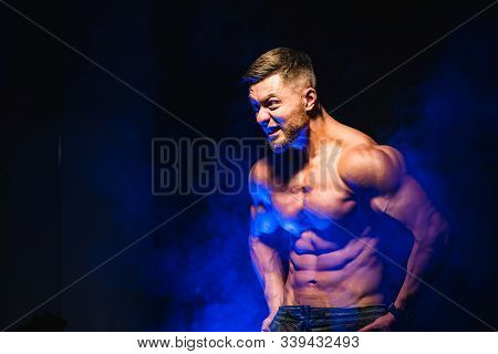 Strong brutal bodybuilder man with perfect abs, shoulders, biceps, triceps and chest showing his biceps. Scream motivation. Blue filter on dark background stock photo