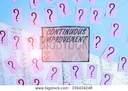 Writing note showing Continuous Improvement. Business photo showcasing ongoing effort to improve products or processes Scribbled and crumbling papers with thick cardboard above wooden table. stock photo