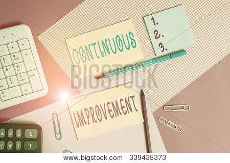 Text sign showing Continuous Improvement. Conceptual photo ongoing effort to improve products or processes Writing equipments and computer stuffs placed above colored plain table. stock photo