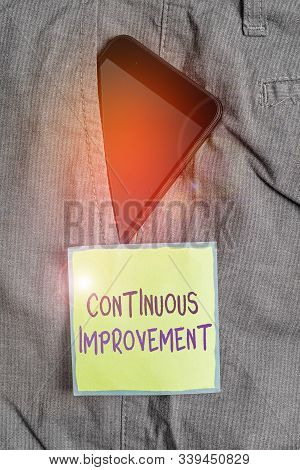 Text sign showing Continuous Improvement. Conceptual photo ongoing effort to improve products or processes Smartphone device inside formal work trousers front pocket near note paper. stock photo