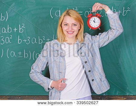 Welcome teacher school year. Looking committed teacher complement qualified workforce educators. School discipline concept. Woman teacher hold alarm clock. She cares about discipline. Time to study stock photo