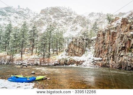 inflatable whitewater kayak and packraft on a shore of mountain river in heavy springtime snowstorm - Poudre River in northern Colorado stock photo