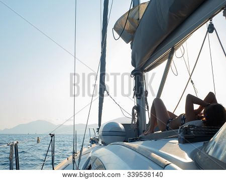 Boat trip on a yacht, A young woman sunbathing on the deck of a sailing boat. fragment of the deck and the mountains on the horizon, the view from the deck stock photo