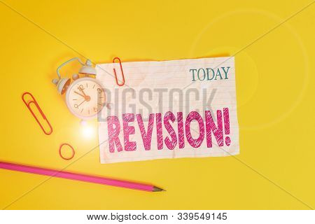 Word writing text Revision. Business concept for action of revising over someone like auditing or accounting Alarm clock clips crushed note rubber band pencil colored background. stock photo