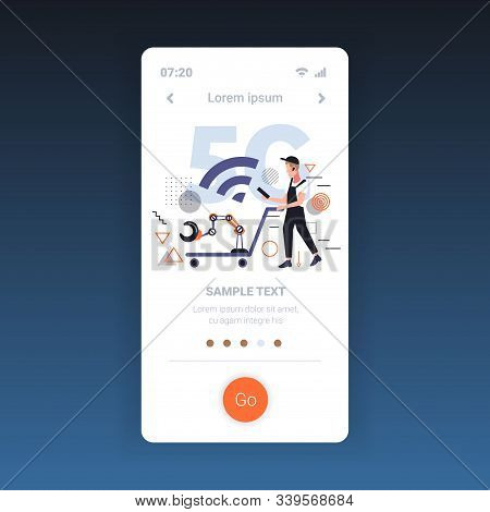 worker in uniform pushing trolley cart with robotic arm using smartphone 5G fifth innovative generation of wireless internet connection concept full length smartphone screen online mobile app vector illustration stock photo
