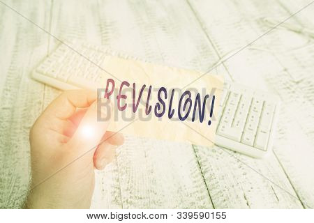 Text sign showing Revision. Conceptual photo action of revising over someone like auditing or accounting man holding colorful reminder square shaped paper white keyboard wood floor. stock photo