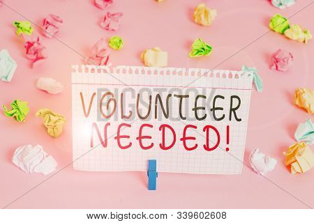 Writing note showing Volunteer Needed. Business photo showcasing asking demonstrating to work for organization without being paid Colored crumpled papers empty reminder pink floor background clothespin. stock photo