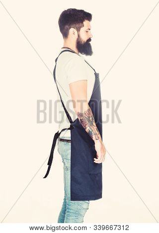 The bushy beard is great. Man with long beard and moustache in profile. Bearded man wearing barber apron. Hipster with stylish beard and mustache hair. Beard barber stock photo