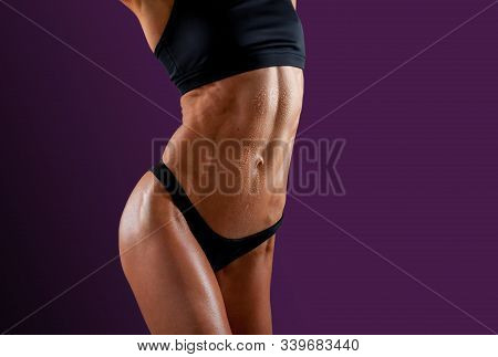 Beautiful super fit young woman showing off her perfect muscular ripped abs. Fitness model. Perfect Slim Body. Studio shot. Fitness trainer with ideal abdominal belly. stock photo