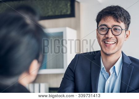 young asian businessman and businesswoman handshake about business agreement at meeting table in modern office.business partnership concept.satisfied the deal with client negotiation stock photo
