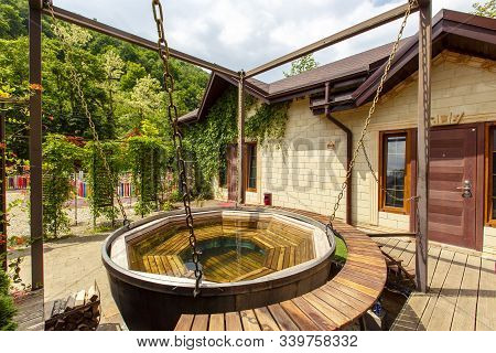Bath tub on firewood, designed for bathing in hot water. The water is heated by wood burning under the VAT. stock photo