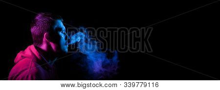Close up portrait of the face of an adult serious man exhales blue toxic smoke while smoking e-cigarette and vape illuminated with pink colored light on a black banner background. Harm to health. stock photo