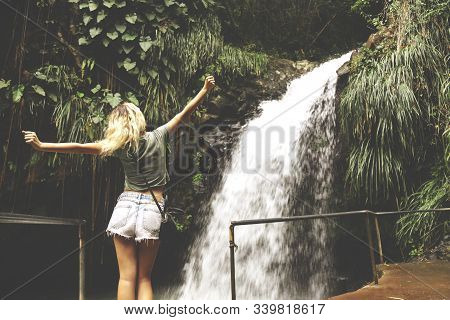 Beautiful view of young woman standing in front of waterfall with her hands raised. Female tourist with her arms outstretched looking at waterfall. stock photo