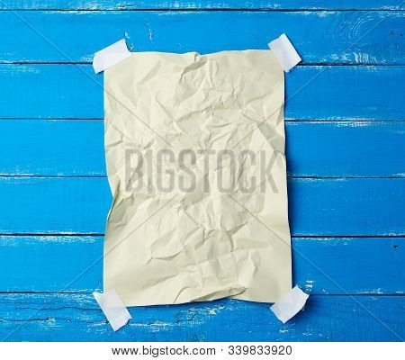glued with adhesive tape in the corners of a rectangular empty beige crumpled sheet of paper on a blue wooden background, place for inscription stock photo
