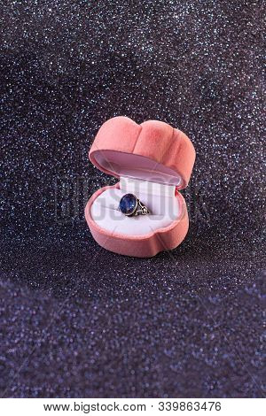 Pink velvet heartshaped box with antique silver ring with blue shiny gem on black glitter background, front view.St. Valentines Day engagement proposal.Copy space, vertical romantic love greeting card stock photo