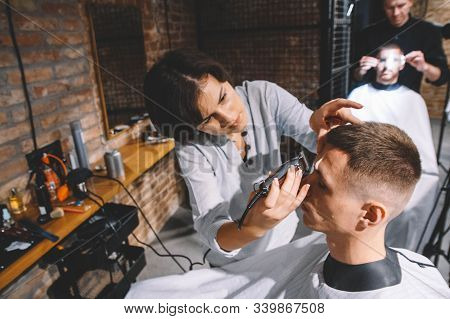 Beautiful woman hairdresser shaves the clients head with a electric trimmer in barber shop. Advertising and barber shop concept stock photo