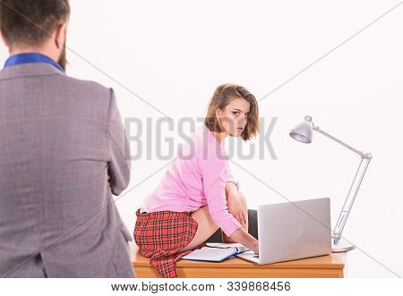 A experienced employee. Professional female employee at workplace against businessman. Adorable woman employee sitting at desktop while man looking at her. Sexy administrative employee or secretary stock photo