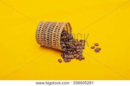Coffee beans spilled from the basket on yellow background stock photo