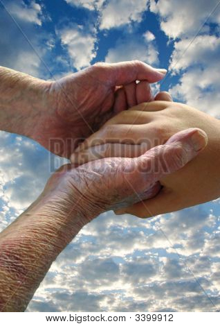 A ninety-year-old man cradles the hand of a young girl against a summer sky. ** Note: Slight graininess, best at smaller sizes stock photo