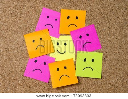 smiley cartoon face expression on yellow post it note surrounded by sad and depressed faces on cork message board in happiness versus depression and smile against adversity concept stock photo