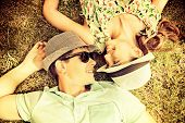 Happy youthful couple unwinding on the grass in a mid year park. Love idea. Get-away.