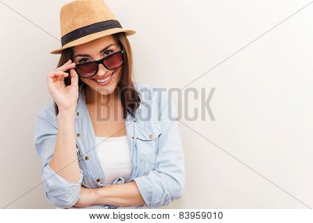 Portrait of beautiful young woman in glasses and funky hat adjusting her glasses and smiling while standing against brown background stock photo