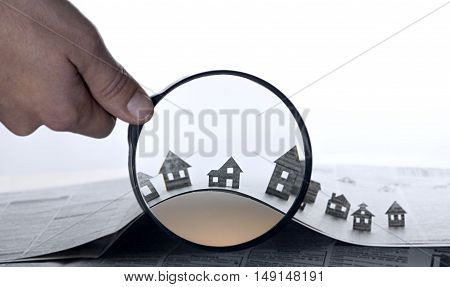 Hand holds the magnifying glass in front of an open newspaper with paper houses. That could mean rent search purchase real estate.