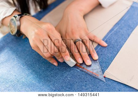 Detail of hands with scissors at tailor shop cutting cloth stock photo