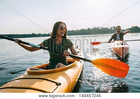 Couple kayaking together. Beautiful young couple kayaking on lake together and smiling