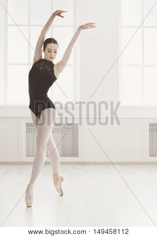 Classical Ballet dancer side view. Beautiful graceful ballerine in black practice ballet positions near large window in light hall. Ballet class training, high-key soft toning. Vertical image